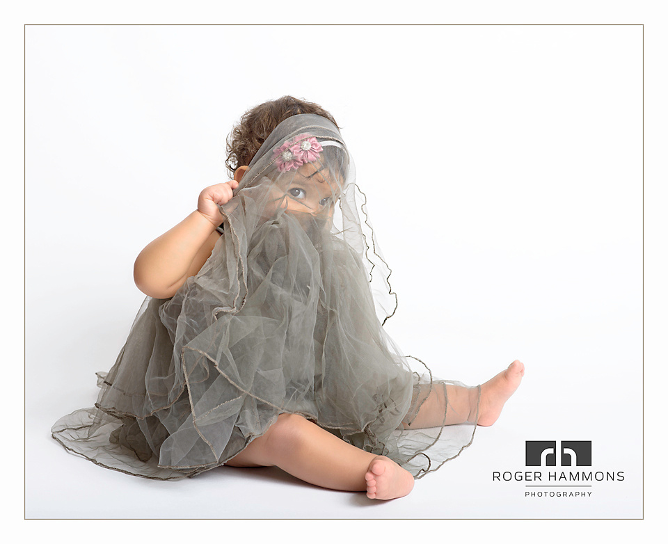 Portrait of one-year-old baby girl with gray tulle dress pulled over her eyes by Ashburn family portrait photographer Roger Hammons