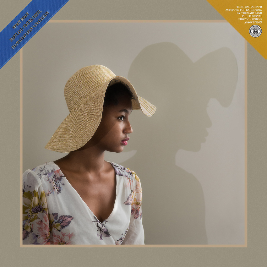 Award-winning natural-light portrait of a teenage girl dressed in summer hat and dress, photographed by Northern Virginia wedding and portrait photographer Roger Hammons whose family portrait studio is located in Ashburn, Virginia
