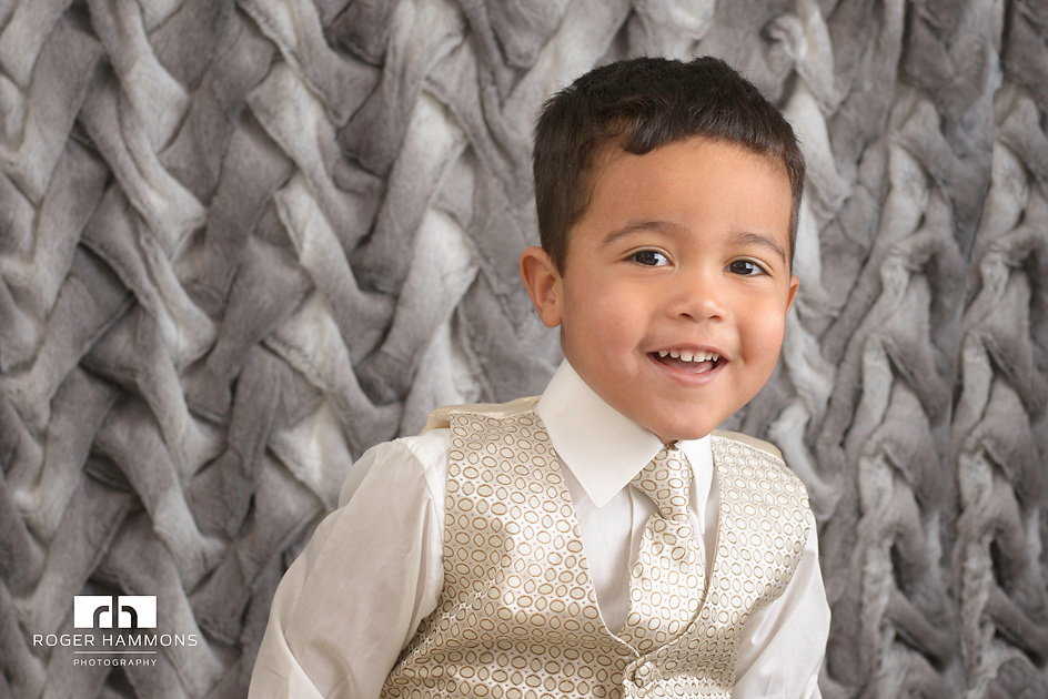 "Northern Virginia wedding and family portrait photographer shares an in-studio portrait of a little two-year-old boy, dressed in vest, tie, and button-down shirt, delighted to pose for the camera being ""fancy""."
