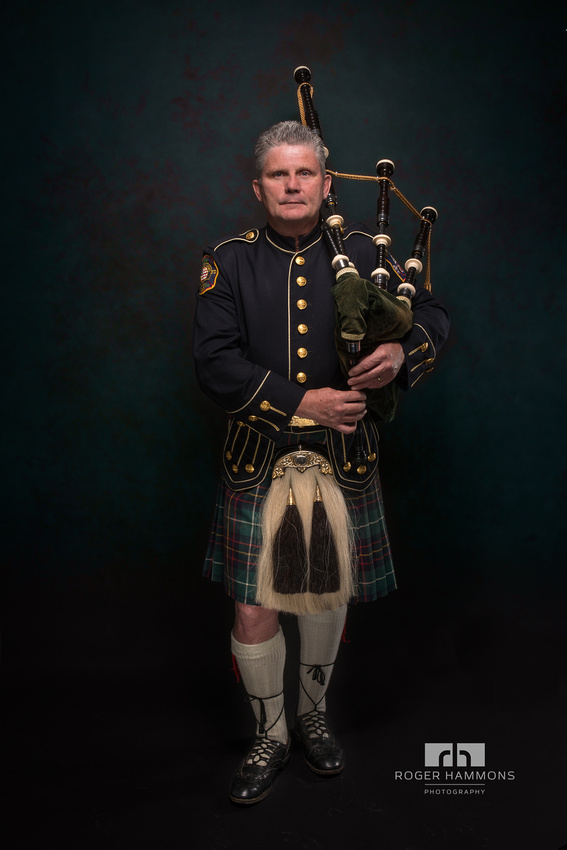 Northern Virginia wedding and portrait photographer shares a studio portrait of a District of Columbia, Maryland, Virginia (DMV) musician Jeffrey Herbert playing the bagpipes in full kilted regalia.