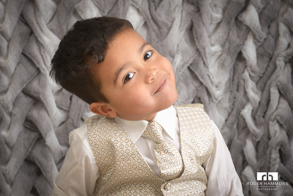 """Northern Virginia wedding and family portrait photographer shares an in-studio portrait of a little two-year-old boy, dressed in vest, tie, and button-down shirt, delighted to pose for the camera being """"fancy""""."""